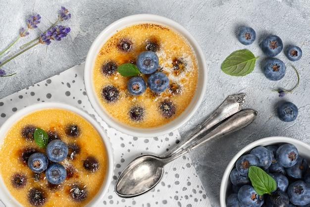 Crème brûlée mit heidelbeere und lavendel, gepudert mit zucker