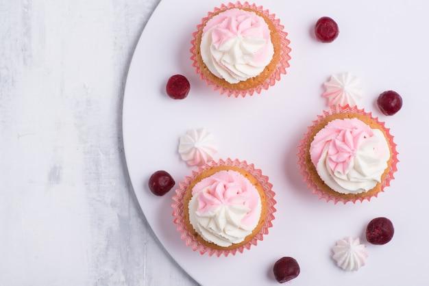 Creme cupcake auf weißem teller, ansicht von oben, nahaufnahme