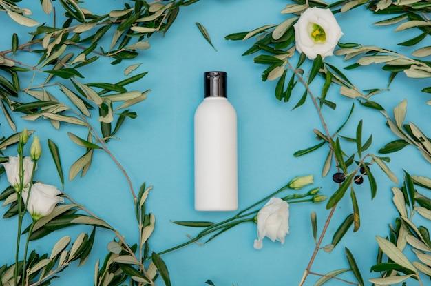 Creme in der flasche mit zweigen der olive auf blauem hintergrund. ansicht von oben