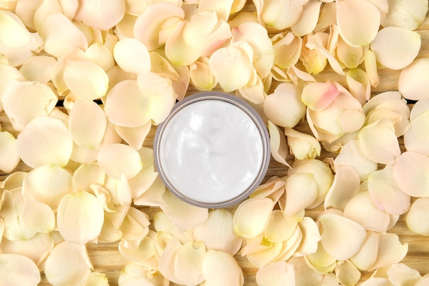 Creme in rosenblättern. kosmetik für gesicht und körper in rosa flaschen mit frischen rosen. spa. ansicht von oben