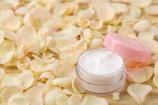 Creme in rosenblättern. kosmetik für gesicht und körper in rosa flaschen mit frischen rosen. spa. platz für text.