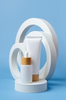 Creme tube mockup und weiße tropfflasche auf podium mit geometrischen formen auf blauem hintergrund