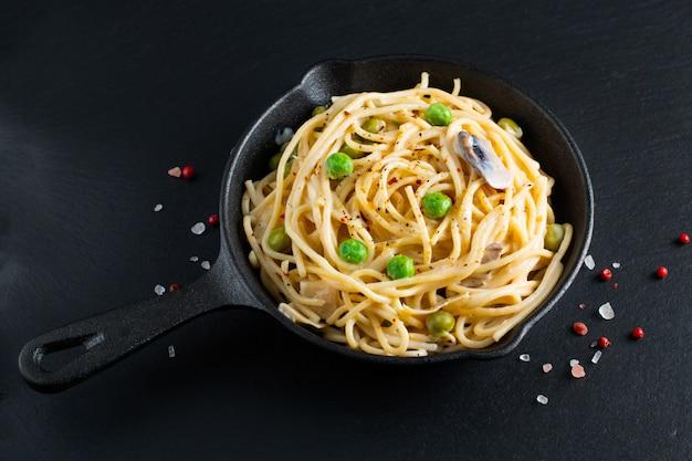Cremefarbene soße des selbst gemachten spaghettis des lebensmittelkonzeptes in der gusseisenbratpfanne