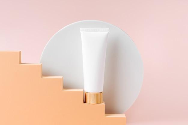Cremefarbenes tubenmodell auf beigefarbenen treppen mit geometrischen formen und podium