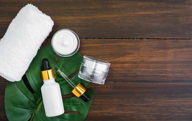 Cremeflaschensatz und serum, modell der schönheitsproduktmarke in der flachen lage