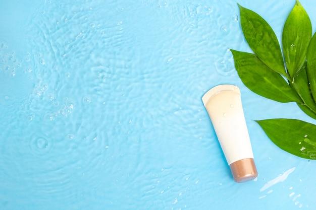 Cremelotion auf die haut mit grünen blättern auf der blauen wasseroberfläche des pools, draufsicht.