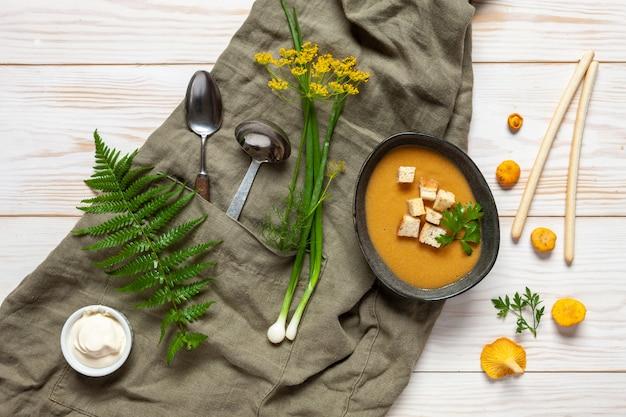 Cremesuppe aus frischen waldpilzpfifferlingen mit croutons.