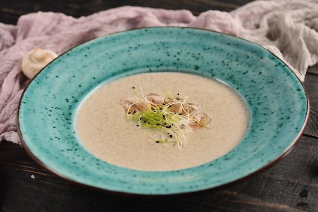 Cremesuppe mit pilzen. in einer blauen platte auf einem holztisch mit dekor