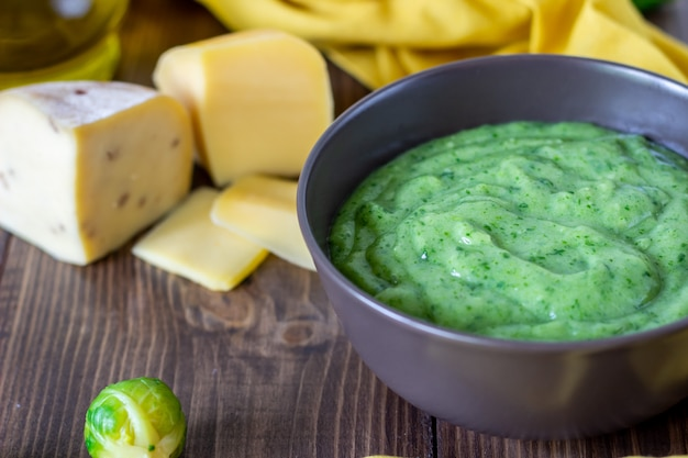 Cremesuppe mit spinat und käse holzoberfläche