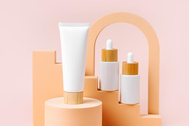Cremetube mit weißen tropfflaschen auf beige treppe mit geometrischen formen und podest