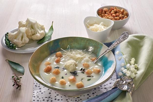 Cremige blumenkohlsuppe in einer blauen tasse mit croutons und parmesan