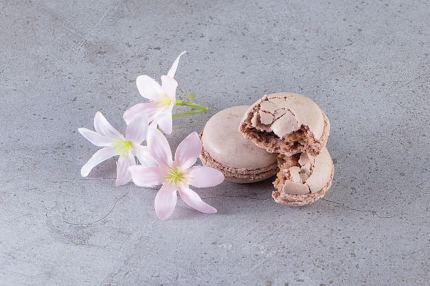 Cremige braune makronen mit pastellblumen auf marmortisch.