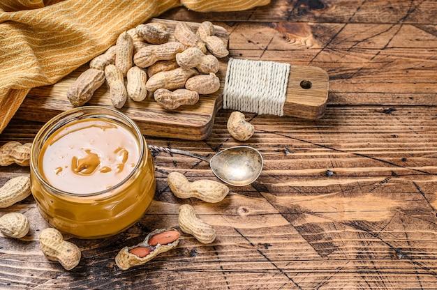 Cremige erdnussbutter im glas auf holztisch