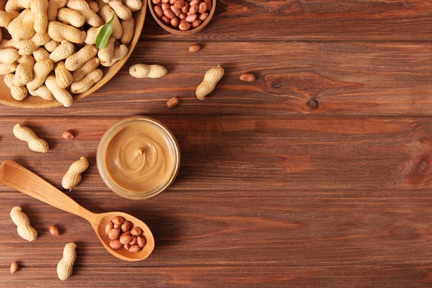 Cremige erdnussbutter und erdnussbohnen auf draufsicht des hölzernen hintergrundes