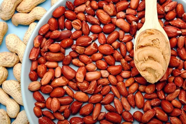 Cremige erdnusspaste im holzlöffel auf erdnüssen. in der nähe der erdnussbutter liegen erdnüsse in der schale und geschälte erdnüsse. die wohnung des minimalistischen essens lag auf dem blauen hintergrund der farbe. lebensmittelhintergrund.