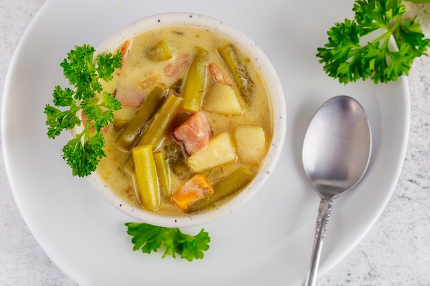 Cremige kartoffelsuppe mit gemüse und löffel. ansicht von oben.
