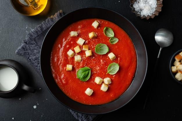 Cremige leckere tomatensuppe serviert in schüssel auf dunklem hintergrund. von oben betrachten.