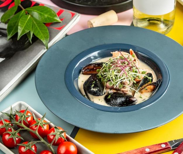 Cremige meeresfrüchtesuppe mit muscheln, garnelen und kleinen tintenfischen