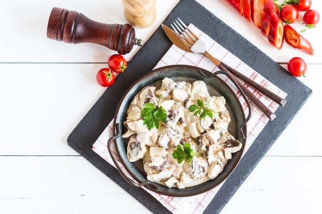 Cremige pilzsauce mit stücken von weißen champignons mit gewürzen in einer pfanne. ansicht von oben. weißer hölzerner hintergrund.