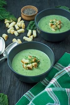 Cremige spinatsuppe mit crackern, kräutern und chiasamen. grüne suppe diente in einer schüssel auf einem holztisch. . flach liegen.