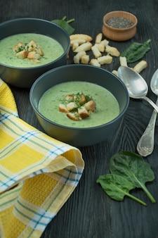 Cremige spinatsuppe mit crackern, kräutern und chiasamen. grüne suppe serviert in einer schüssel auf einem holztisch.