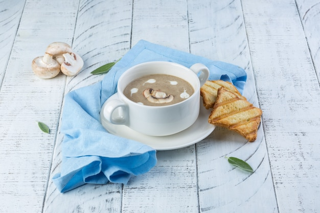 Cremige suppe mit pilzen und toast auf weißem holztisch. kopieren sie platz