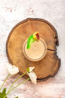Cremiger cocktail der draufsicht in kleinem glas mit blumen auf weißem schreibtischcocktailcreme-farbfoto-dessert