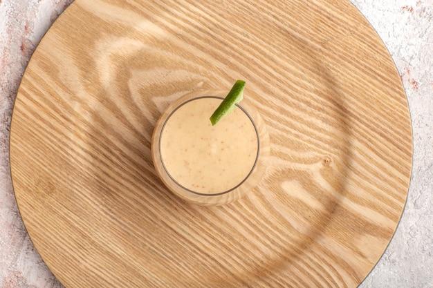 Cremiger cocktail der draufsicht innerhalb des kleinen glases auf dem farbfoto der weißen wandcocktailcreme