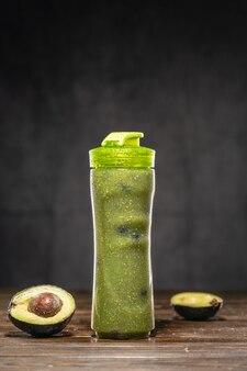 Cremiger grüner avocado-bananen-smoothie mit blaubeeren in klarer smoothie-flasche