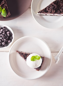 Cremiger käsekuchen mit schokolade, schwarzer johannisbeere, eis und minzblatt zur dekoration