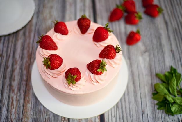 Cremiger kuchen mit erdbeeren auf einem holztisch