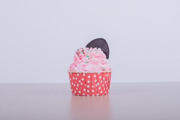 Cremiger rosa cupcake auf weiß