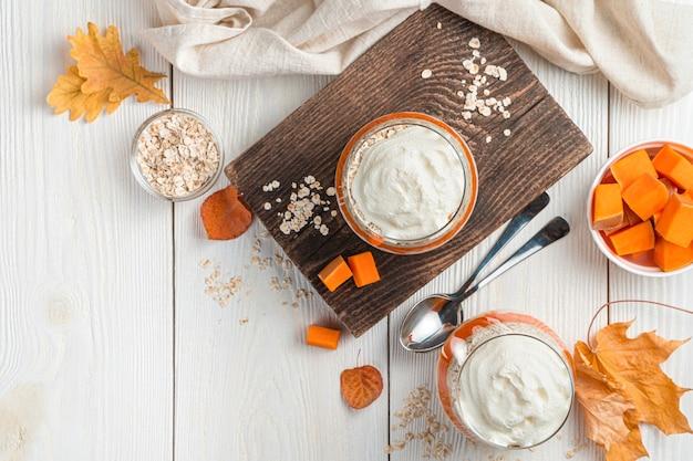 Cremiges dessert mit kürbis und getreide auf weißem hintergrund mit blättern vegetarisches herbstdessert