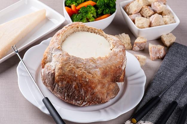 Cremiges käsefondue im italienischen brot auf tellern mit brokkoli, brot und käse