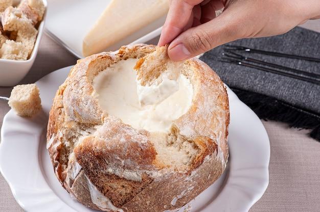 Cremiges käsefondue in italienischem brot und eine hand, die brot hineintaucht