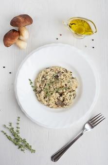 Cremiges risotto mit arborio-reis, der pilze und thymian auf weißem holztisch enthält