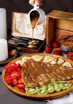 Crêpe mit schokoladensauce und geschnittenen erdbeeren, kiwi und bananen
