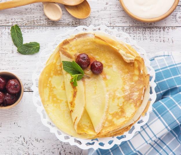Crepes (blini) und honig auf hölzernem hintergrund, draufsicht, kopienraum. hausgemachte dünne crepes zum frühstück oder dessert.