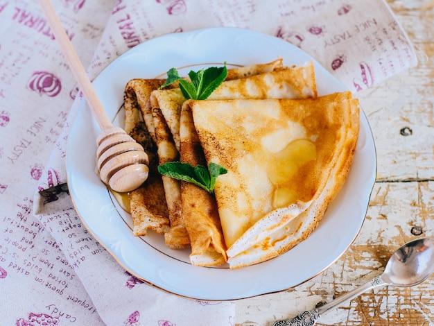 Crêpes, dünne pfannkuchen mit honig und minze auf einem weißen teller