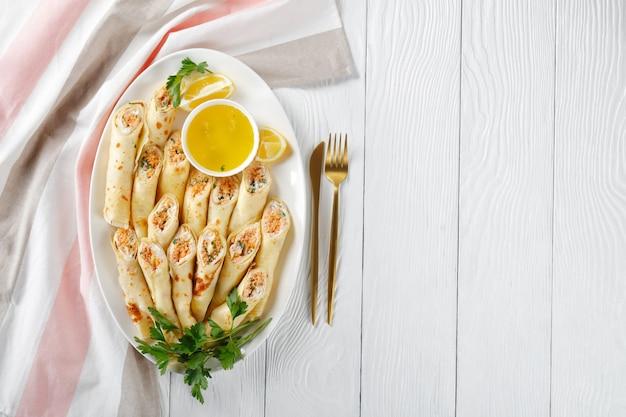 Crepes gefüllt mit frischkäse und lachs, petersilie serviert auf einem weißen teller auf weißem holzhintergrund