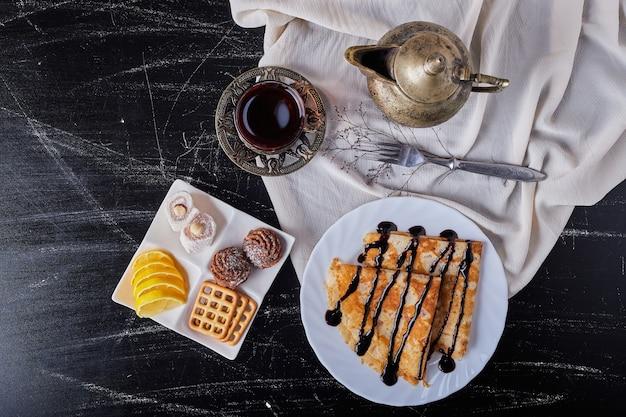 Crepes in einem weißen teller mit schokoladensirup und tee.