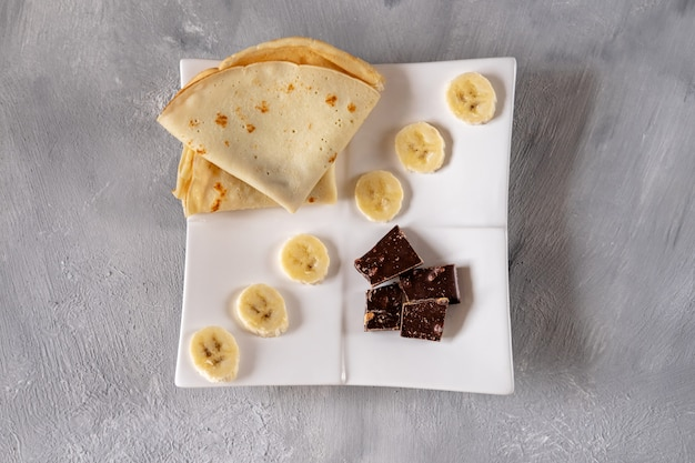 Crepes mit banane und schokolade auf einem weißen teller