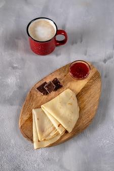 Crepes mit himbeermarmelade und schokolade auf einem holzbrett