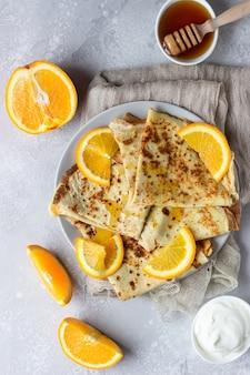 Crepes mit orangen, honig und naturjoghurt oder sauerrahm. dünne pfannkuchen.