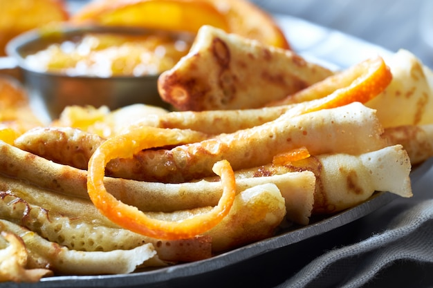 Crepes suzette, nahaufnahme auf vintage metallplatte serviert mit orangensauce