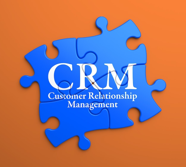 Crm - customer relationship management - geschrieben auf blauen puzzleteilen. unternehmenskonzept.