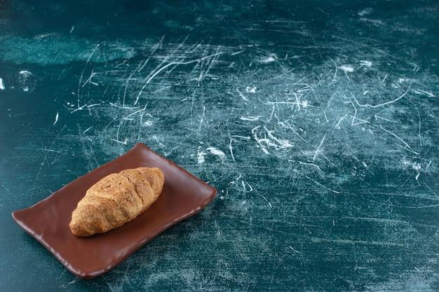 Croissant auf einem braunen teller auf blauem hintergrund. foto in hoher qualität