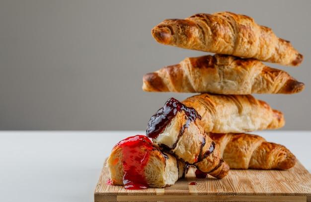 Croissant auf einem schneidebrett mit marmeladenseitenansicht