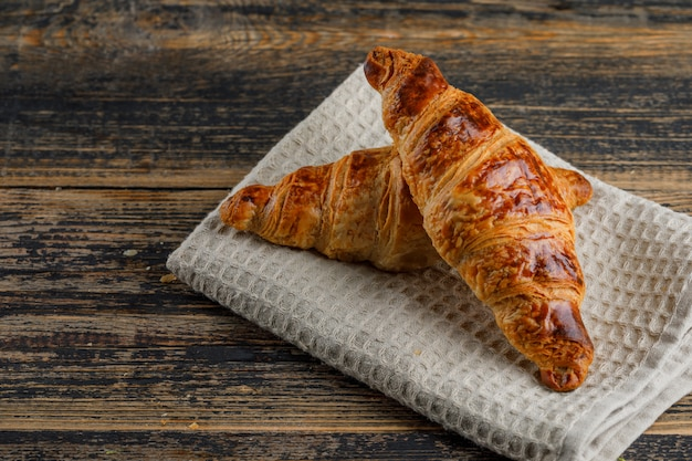 Croissant auf holz- und küchentuch, blickwinkel.