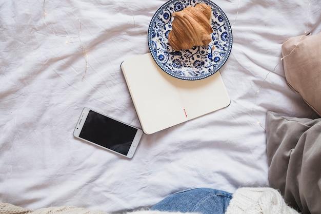 Croissant auf platte nahe notizbuch und smartphone